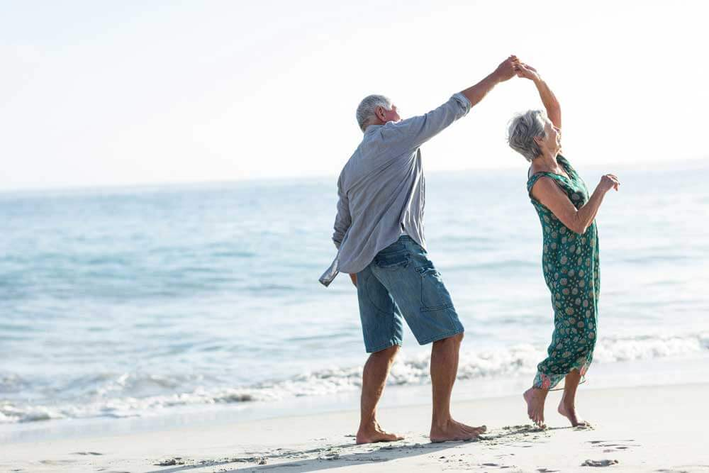 man and woman dancing on the beach